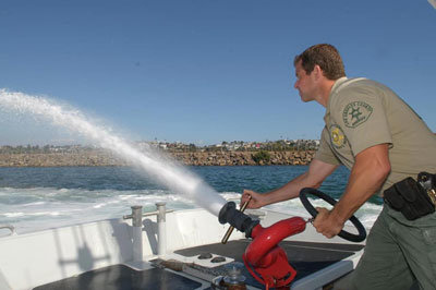 Deputy operating Water hose on boat in harbor