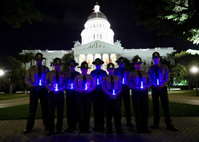 Deputies holding blue lights in front of capital at night