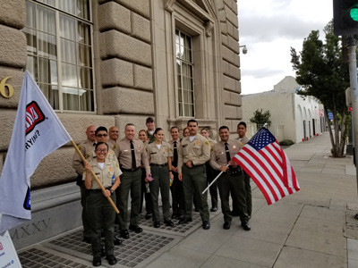 Sheriff Villanueva pictured next to deputies holding up flags