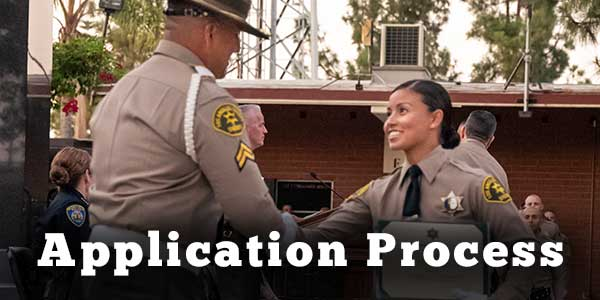 Deputy shaking hands with an instructor at graduation