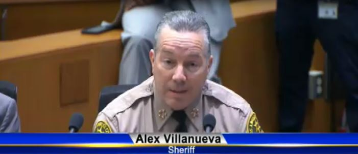 Sheriff Alex Villanueva behind a microphone