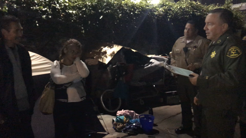Sheriff Villanueva speaking to a man and woman in an alley