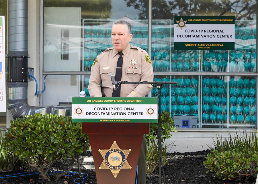 Sheriff Alex Villanueva Speaking at a podium infront of thousands of masks inside a decontamination Center.