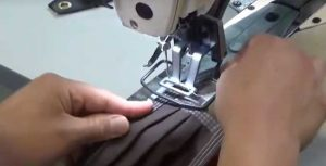 Close up of hands worning on a Sewing machine.