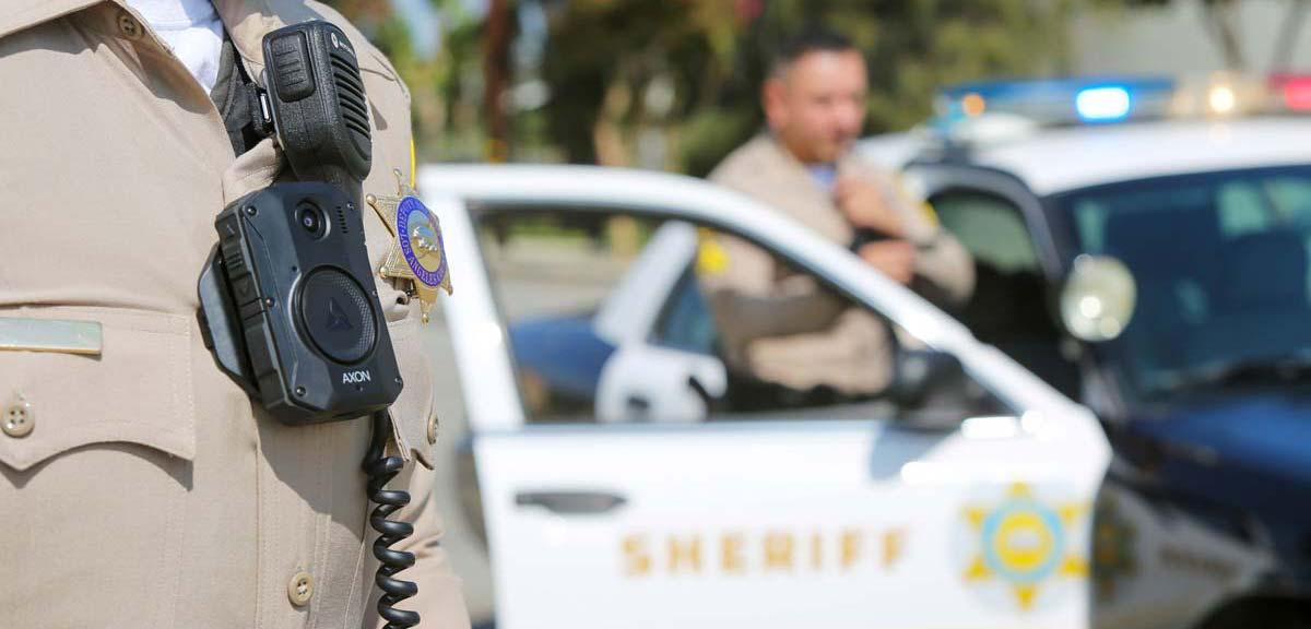 deputy wearing body worn camera standing in front of Patrol car