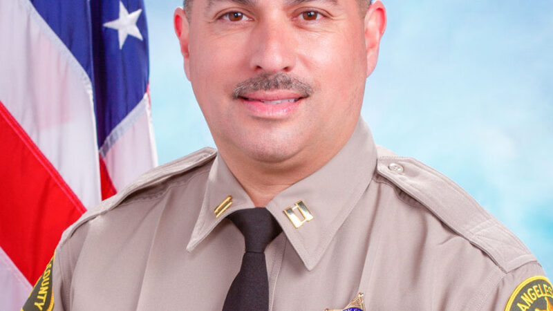 Portrait of Captain Mark Reyes in uniform, sitting infront of the American Flag