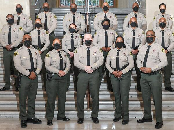 Sheriff standing with staff in the hall of the Hall of Justice building