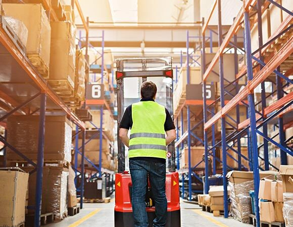 Person in working vest pulling items from large warehouse