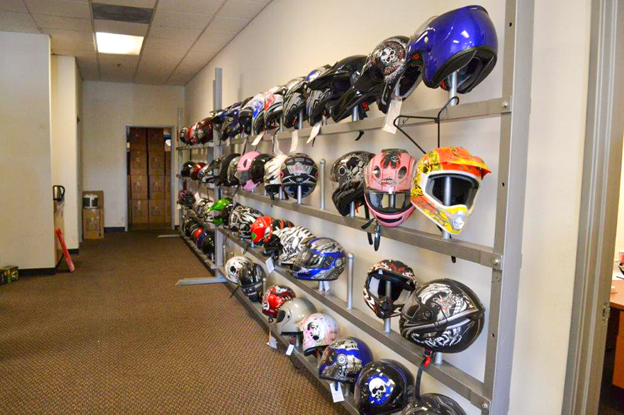 Image of 40 or 50 fake motorcycle helmets displayed in an office. The Helmets are on a wall rack along the wall.