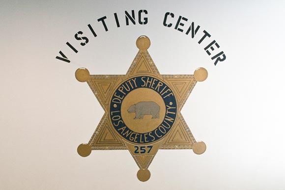 """Picture of hand painted sheriff's badge, painted on a white wall in the C R D F Jail. The words above read, """"Visiting Center""""."""