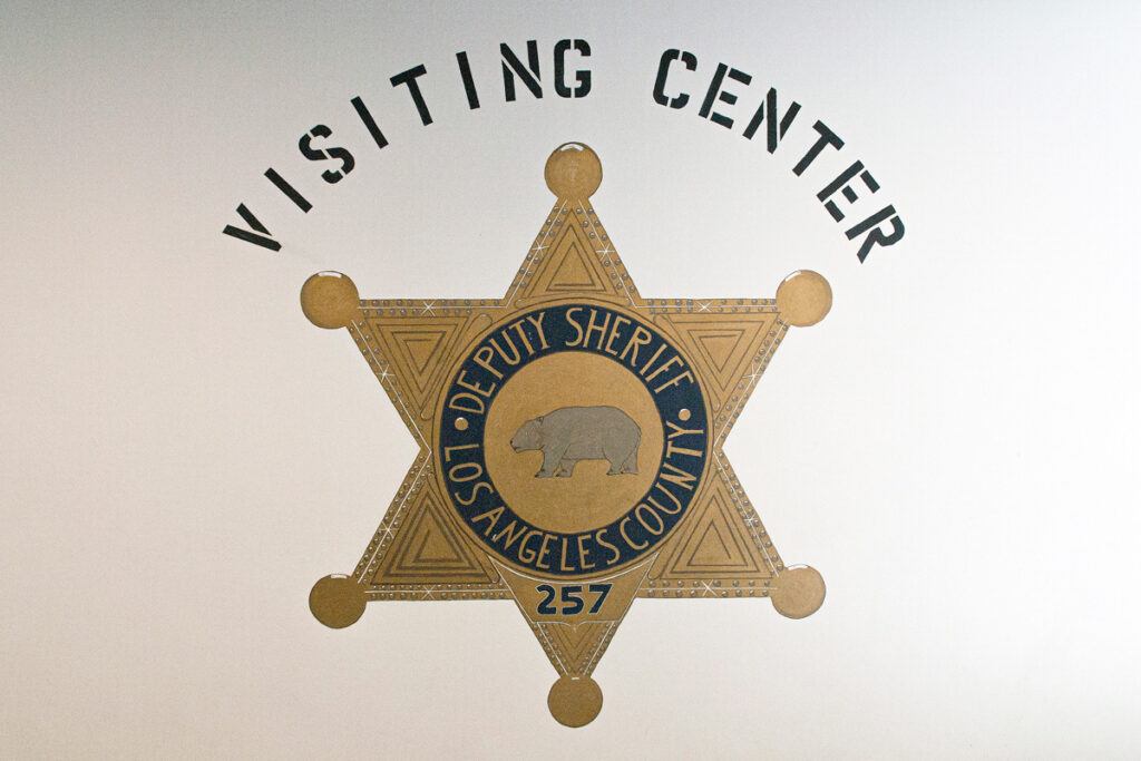 "Picture of hand painted sheriff's badge, painted on a white wall in the C R D F Jail. The words above read, ""Visiting Center""."