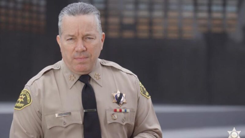 Picture of Sheriff Villanueva in uniform stading infront of the LASD Memorial Wall addressing the camera.