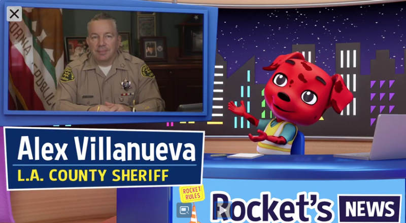 Picture of Rocket Safety Spokes dog interviewing Sheriff Alex Villanueva, Rocket is seated at a desk and the Sheriff is in a screen over rocket's shoulder. Rocket is an animated dog, with red fur