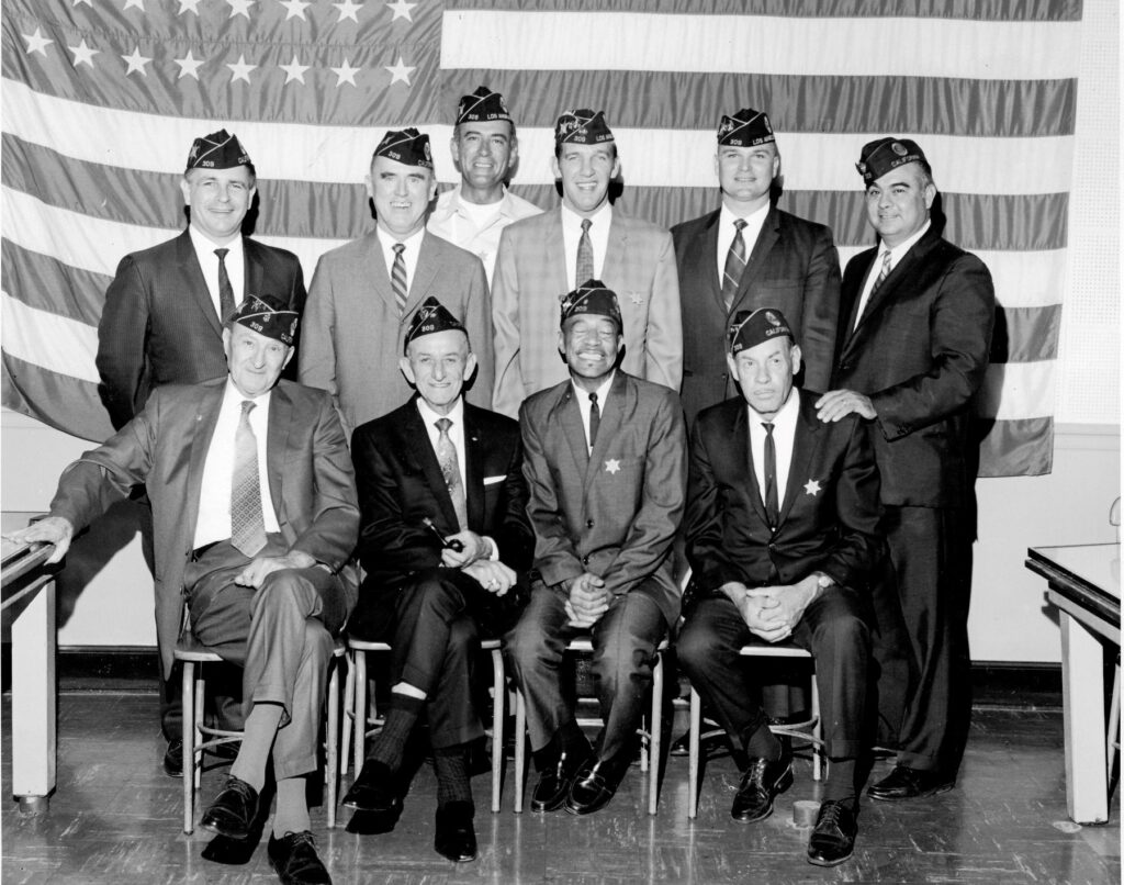 vintage black and white photo of 10 men in stuits with legion cover hats on. Posing shoulder to shoulder infront of a wall sized american flag.