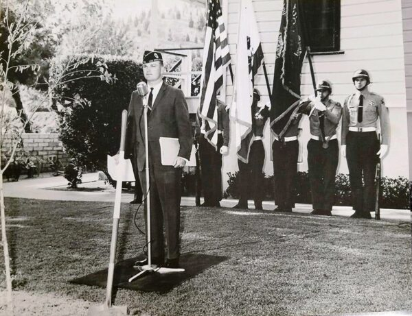 vintage image of Vetter in unifom stading infront of soldier color guard holding flags.