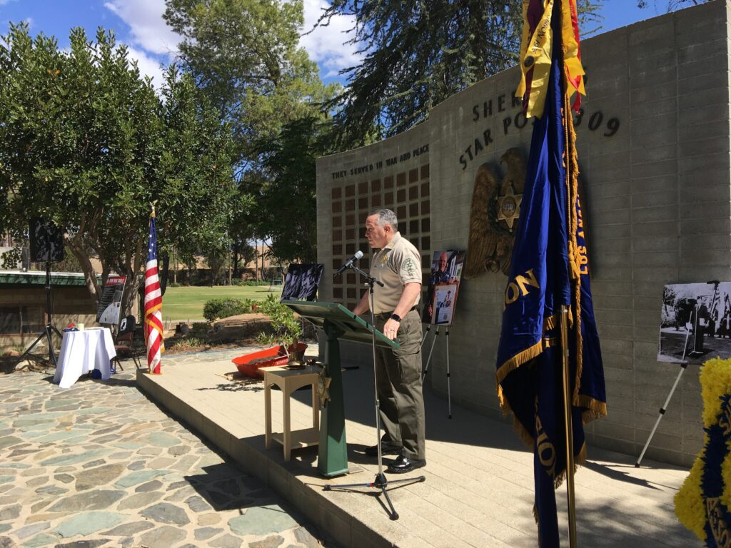 Image of Sheriff Alex Villanueva giving speach infront of the Star Post Memorial wall at a podium between the american flag and the American Legion flag.