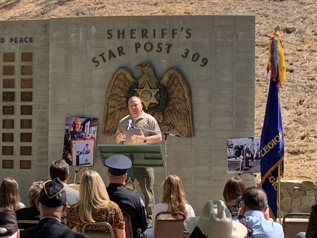Sheriff Alex Villanueva standing infront of the Star Post 309 Memorial wal giving a speech infront of a crowd.