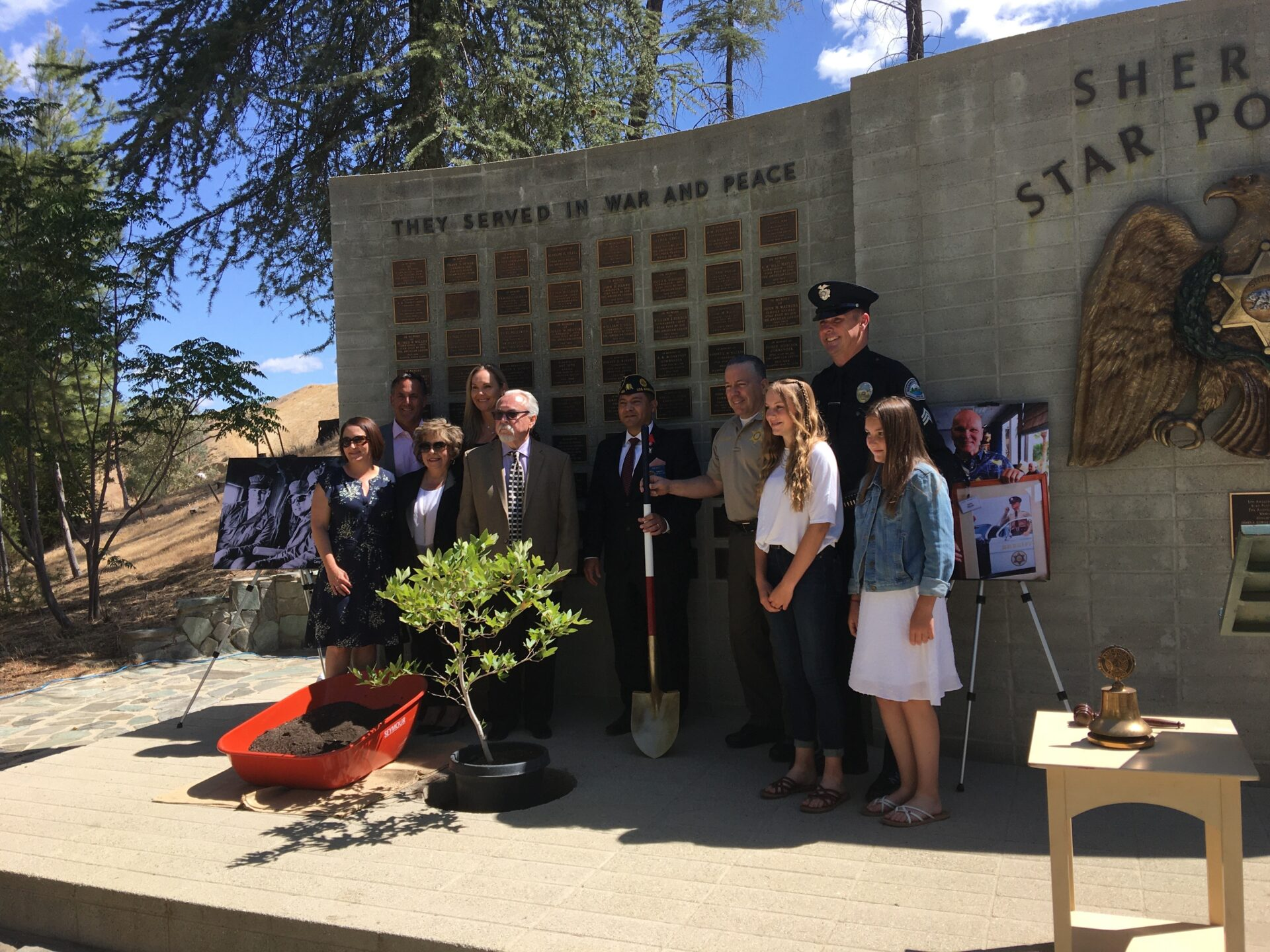 Family standing in front of memoral wall, small tree is being planted, Sheriff Alex Villanueva is holding a shoval.