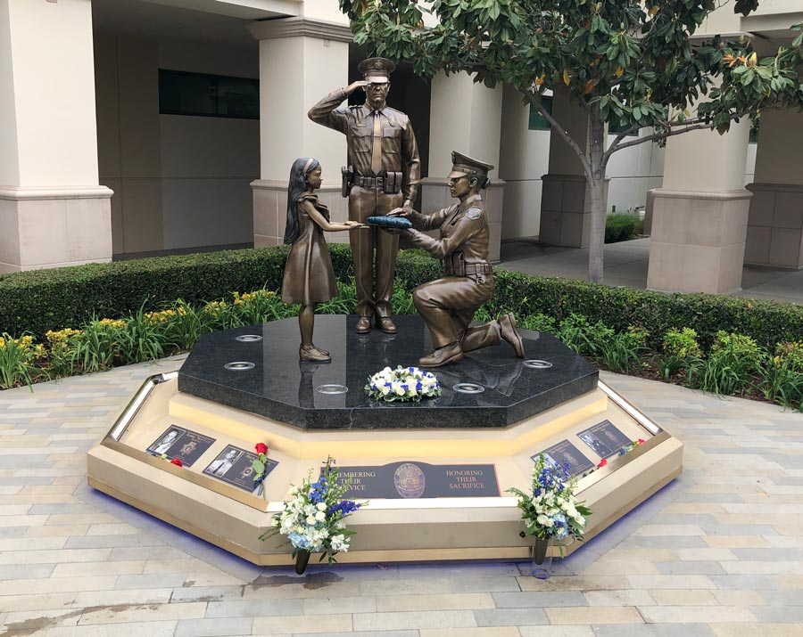 Image of the Buena Park Police departent memorial of fallen officers. Bronze statue of a saluting officer, another officer on one knee presenting a folded flag to a little girl. all cast in bronze.