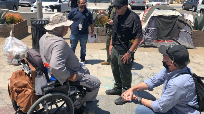 MET team deputy helping a homelss man in a wheelchair. there are three people from Vetran affairs talking to a man in a large white sun hat, he is dressed in a long sleeve gray shirt,the wheel chari has an orange backpack on the back, the homeless man is in his 60s.