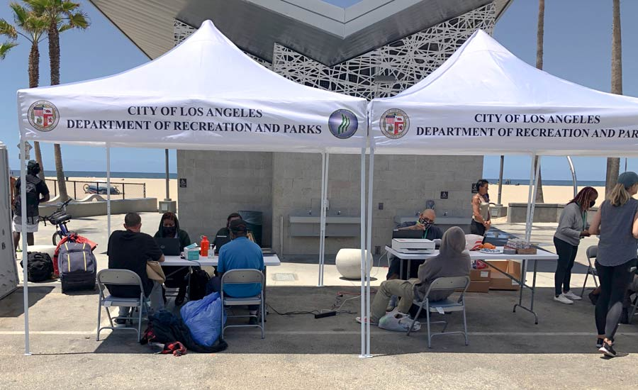 """Two white easy ups with the words """"City of Los Angeles Department of Recreation and Parks"""". There are tables set up underneith in the shade. Social workers are sitting and talking to over 4 homeless people who need various services."""