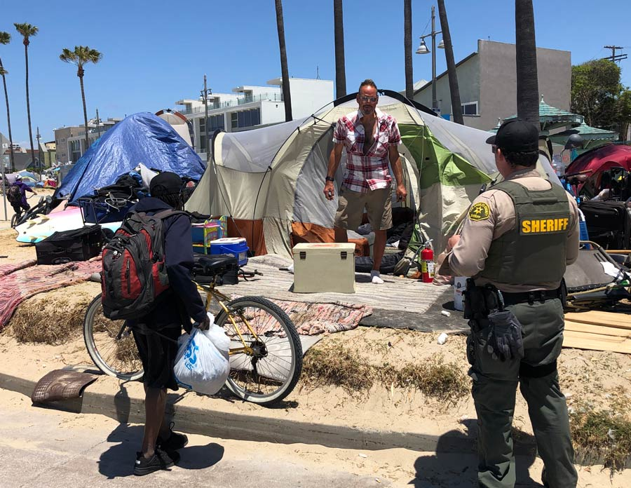 Image of a Deputy talking to a man that is walking out of a tent that is se tup among many other tents that are on the sand, the man is dressed in a short sleeve plaid red shirt with tan shorts, he is wearing aviator sunglasses. There is another man stanind next to the deputy holding bags fo items next to a bike.