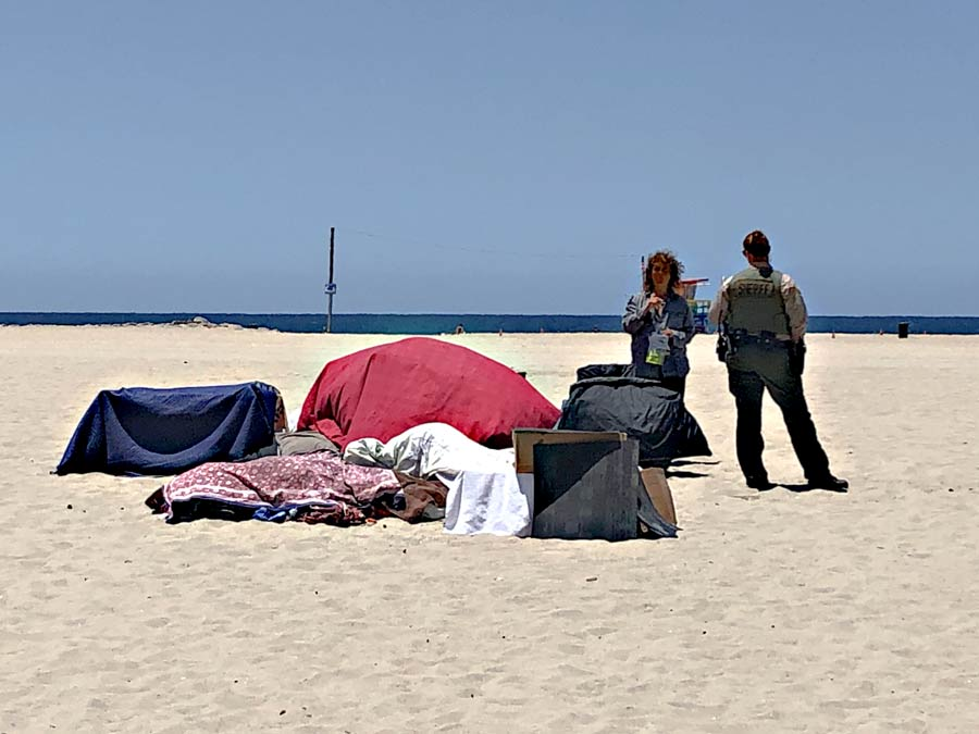 There are two shelters made of blankets on the sand next too the water. A woman is talking to a female deputy. there are other belongings next the the camp site. A life guard tower is visible just infront of the water's edge.