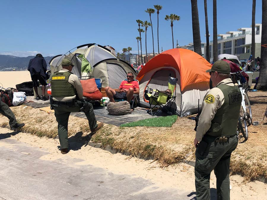 Two Deputy sheriffs are talking to a man sitting in a lawn chair, the man in the chair is set up infront of a row of tents. There are bikes near the camp sites.