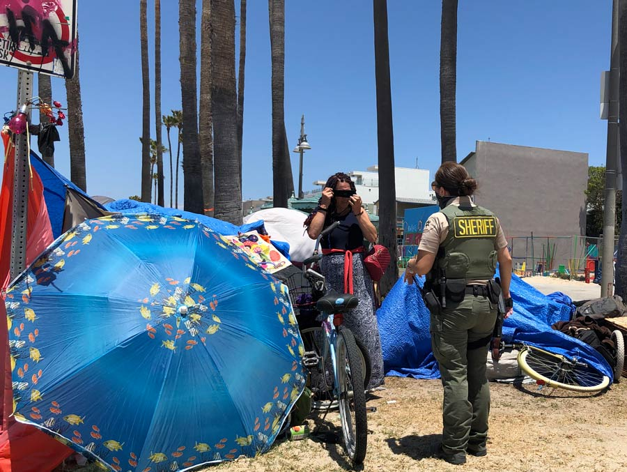 A female Deputy is talking to a woman in a black shirt an paisly blue pants she is in a camp site among shelters made of large umbrellas and tarps, there are belongings strewn about the site and bikes laying on their side aswell as a spraypainted on parking sign,