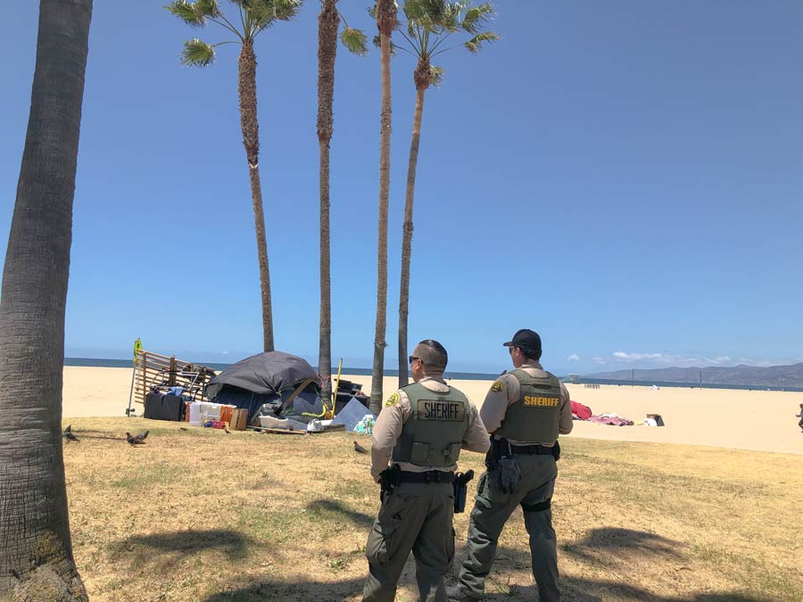 Two deputies are looking over the venice beach from a grassy area that is in front of the sand, there is a black tent set up on the sand and beach towels on the beach with people playing on the sand.