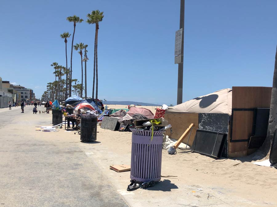 Image of Veince boardwalk with large amount of trash falling out of trashcans, and rows all along the boardwalk of tents and make shift shelters. there are people jogging with dogs and playing