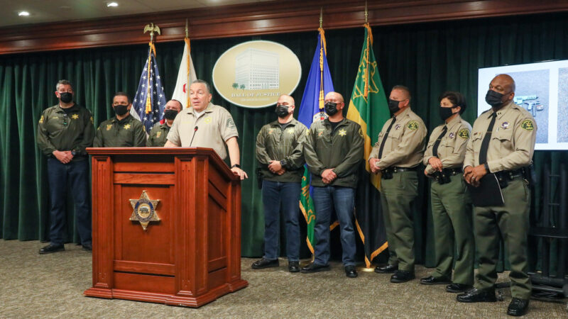 picture of Sheriff Alex Villanueva standing at a podium speaking to the audience. The podium is brown and has the Sheriff's Badge on the front. There are 8 other personel from O S S behind the Sheriff. A screen is off to the right behind O S S Captain with pictures of two guns on the screen.