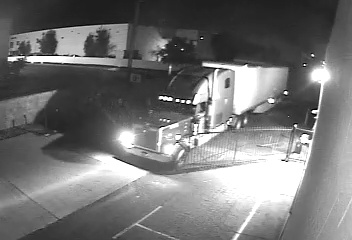 image of black and white security camera footage of a large Semi Rig driving through a ro Iron Gate in a back alley of a business. The semi has its lights on and is pulling a long 45 foot white trailer.