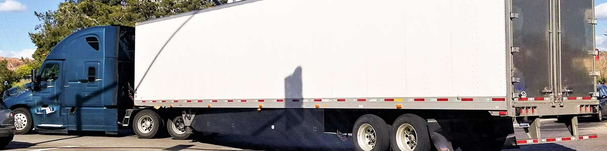 Image of a blue semi with a white 54 foot trailer pulling through an intersection on a city street.