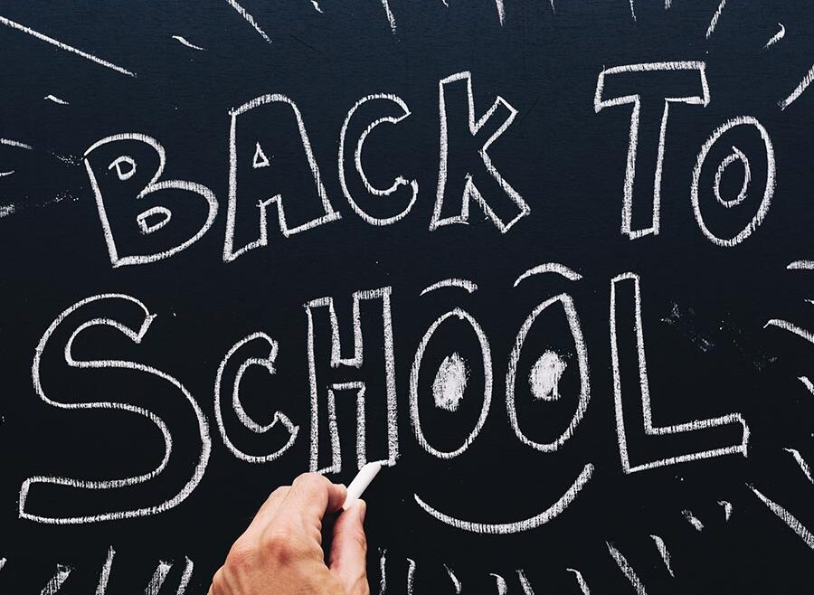 """image of a hand writing on a chalk board, the board reads """"BACK TO SCHOOL"""" and has a smile under the two o in the word """"School""""."""