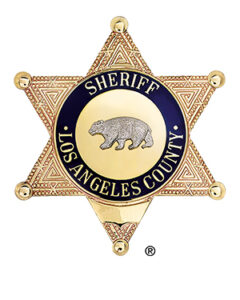 """image of the Sheriff's Badge. Gold 6 point star. blue circular band with gold letters that reads """"Sheriff, Los Angeles County"""". An engraving of a Bear is in the center."""