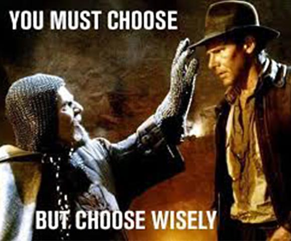 """Still from """"Indiana Jones and the Holy Grail"""" A knight in chain mail and armor is reaching up to Indiana Jones' face. The caption is, """"You must choose, but choose wisely."""""""