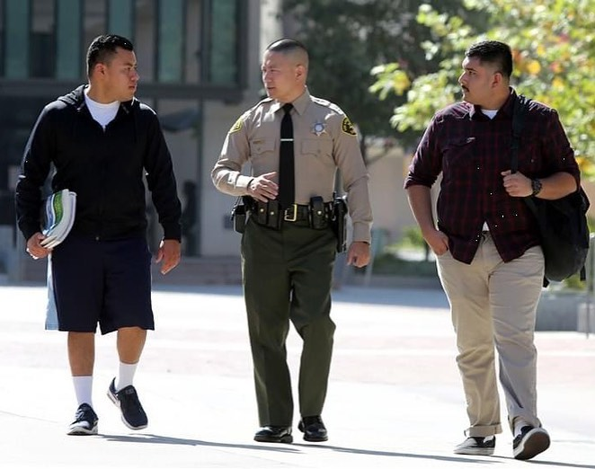 deputy sheriff is walking with two hispanic men down the street towards a camera. They are having a friendly conversation. The Deputy is wearing a tan longsleeve shirt with a black tie and green pants. there are two men on either side of the deputy. They are holding books and a backpack.
