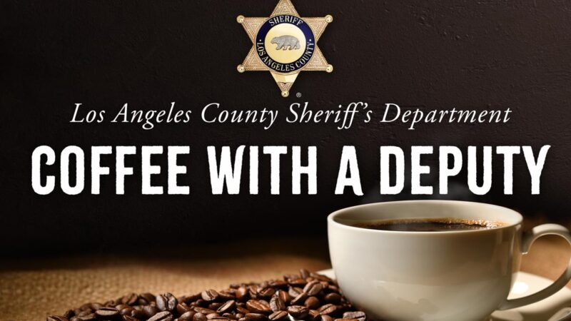 """Image of a coffee cup on a plate, the plate is covered with coffee beans. Everything is sitting on a burlap material. At the top there is a Sheriff's star, gold six point star with an engraving of a bear in the middle. The text reads """"Los Angeles County Sheriff's Department, Coffee with a Deputy"""""""