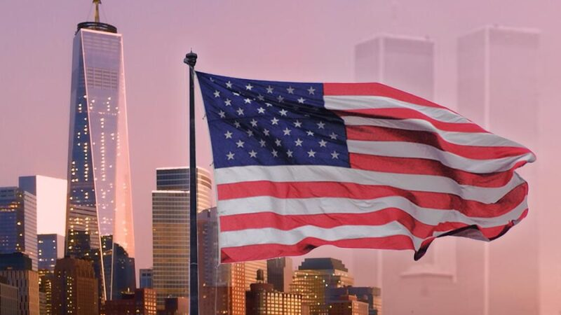 We Will Never Forget, September 11, 2001. Image of the american flag waving over the One Trade Center Tower on the left of flag and the Right side of flag are the Twin towers very faint over the orange purple sky.